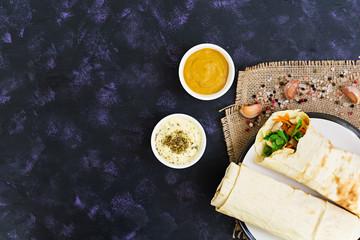 Shawarma sandwich with ingredients on dark background. Top view
