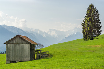 View from wooden barn to snow covered mountains in springtime