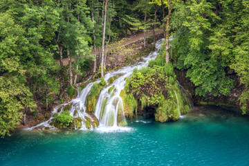 Tourist route in the green summer forest with waterfall, Plitvice Lakes National park, Croatia. Nature background suitable for guide book