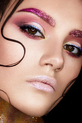 Young girl with creative makeup and shiny eyebrows. Beautiful model with strands of hair on face and perfect skin. Beauty of the face. Photo taken in studio. Shining neck, covered with sequins. Macro
