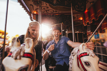 Young couple having fun on carousel
