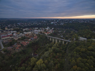 Aerial shot of the canyon of the Smotrych River towards the Novoplanivskyi Bridge in Kamianets-Podilski Ukraine. The shot is taken in autumn with the canyon trees looking colourful