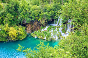 Waterfall in the green summer forest with turquoise water of the lake at Plitvice National park, Croatia. Nature background suitable for wallpaper, cover or guide book