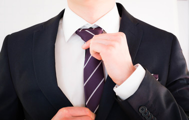 Geschäftsmann richtet seine Krawatte mit beiden Händen