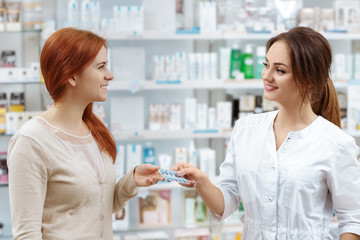 Helpful advice. Attractive smiling pharmacist giving her client pills at the local drug store.