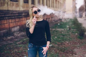 Vaping. Young beautiful woman vaping . Vapor concept.