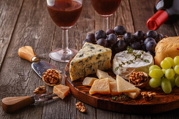 Cheese, nuts, grapes and red wine on wooden background.