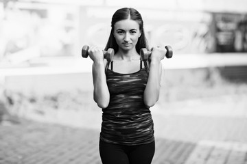 Girl with dumbbells engaged in fitness