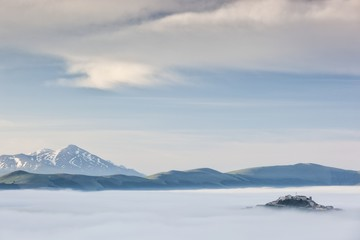 Low cloud over rolling hills and the small village of Castelluccio di Norcia, Umbria, Italy