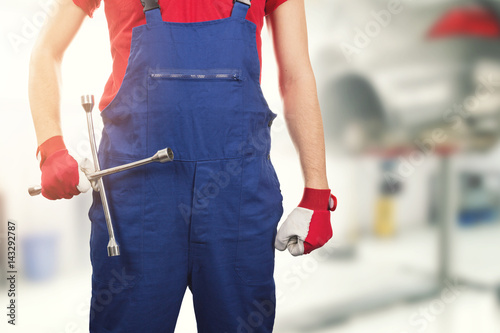 auto mechanic with tire wrench in hand in car service