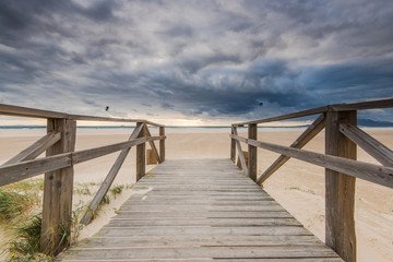 wooden bridge on beach with dark clouds before storm