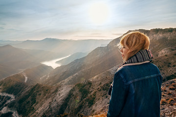 Beautiful girl on top of mountain watching sunrise