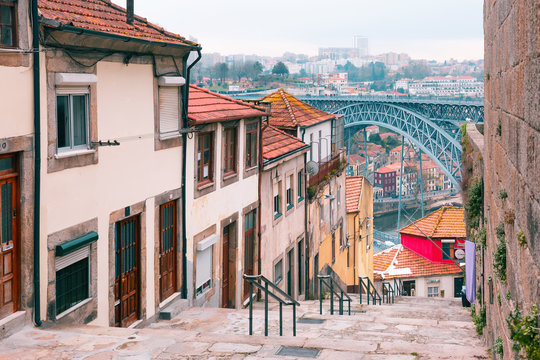 Traditional old houses in Ribeira and stairs down to the river Douro, Dom Luis I or Luiz I iron bridge on the background, Porto, Portugal