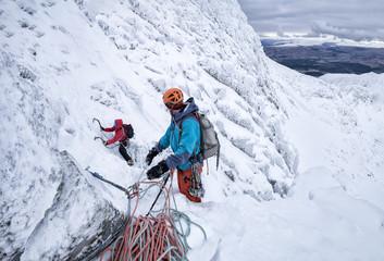 Scotland, Anoach Mor, Man ice climbing in winter