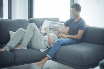 Young couple with tablet relaxing at home