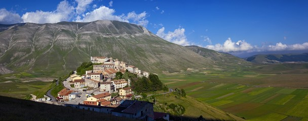 The olf village of Castelluccio before the disastrous earthquake of 2016 in the background the fields planted with lentil, Italy