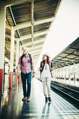 Hipster couple walking on platform at the train station. Two young tourist are ready to get on the train and begin their journey. Travel concept.