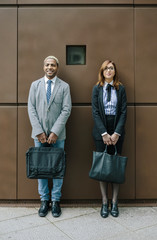 Young businessman and woman standing in front of steel wall