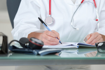physician writing prescription-cropped image