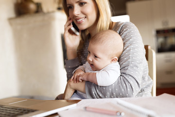Smiling mother with baby at home on the phone
