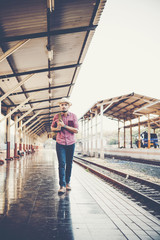 Young tourist man with backpack standing on platform waiting for train at train station, vintage tone filter effects.Travel concept.