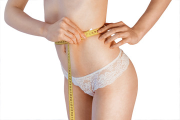Woman measuring her waistline. Perfect Slim Body. Diet. Young girl measuring waist with a white background