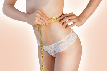 Woman measuring her waistline. Perfect Slim Body. Diet. Young girl measuring waist with a beige background