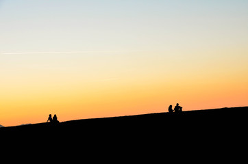 Silhouette of two couples at sunset on the beach