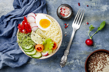 Veggies detox Buddha bowl recipe with egg, carrots, sprouts, couscous, cucumber, radishes and seeds. Top view, flat lay, copy space