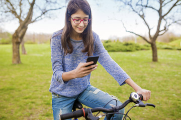 Teenage girl with bicycle in city park use smart phone