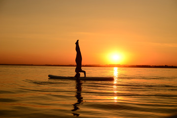 Beautiful young sporty woman is training upside down on the surf desk at sunset time