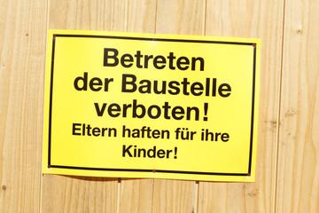 Gelbes Schild Betreten der Baustelle verboten an einem Bauzaun