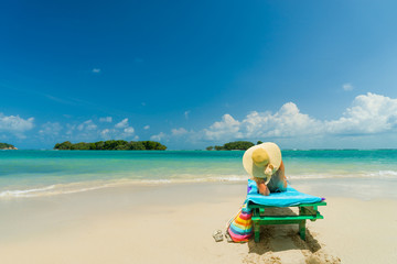 Woman sitting on a chair at the beach