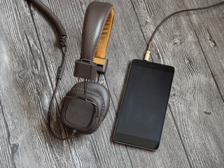headphones connected to the smartphone. wooden background