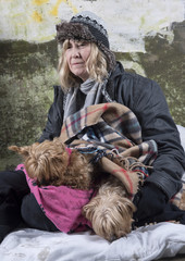 Mature homeless woman with a Yorkshire terrier leaning against an old wall