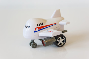 Closeup of white plastic toy airplane on a white table.