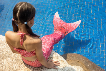 Mermaid girl with pink tail on rock at poolside put feet in water