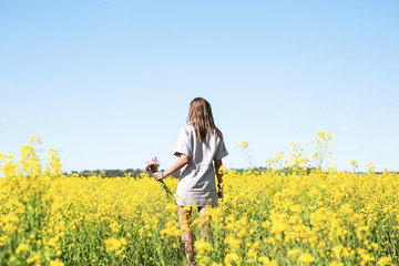 Woman in canola field holding flowers