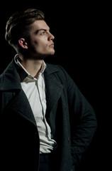 Handsome man posing in white shirt and dark coat