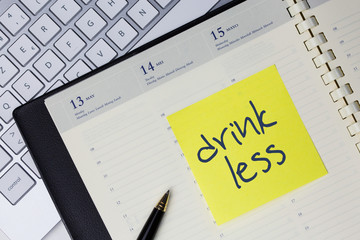 Paper note with the words - Drink less - in business desk. How to get better concept