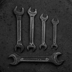 Set of black & white wrenches on black background
