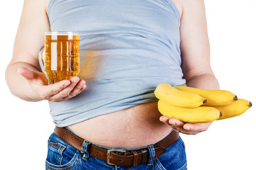 The belly of a fat man isolated on white background. A man stands before a choice of the beer or fruit. The concept of healthy and proper nutrition.