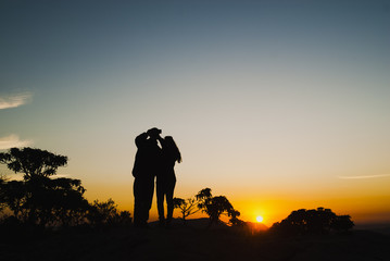 Couple silhouette doing self at sunrise in Brazil