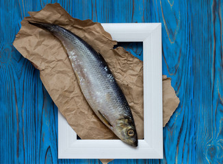 Fish in frame on blue wooden table. Top view.