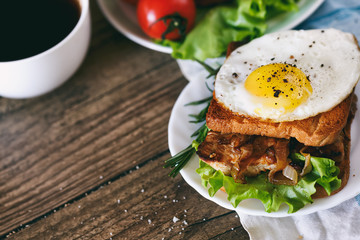 Sandwich with eggs, chicken, cucumber and lettuce on a wooden background. Selective focus. copy space