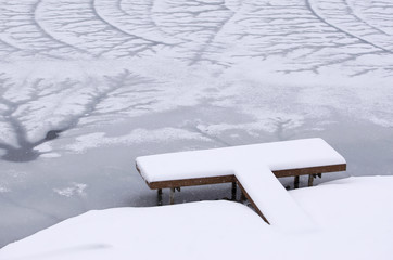 Snow covered dock on frozen lake