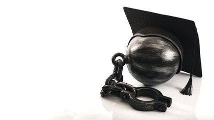 Student debt concept with ball and chain wearing graduation cap symbolizing the burden tuition costs represent for students attending college or university on credit, with copy space isolated on white