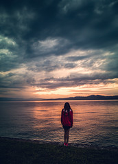Lonely girl on the lake shore during the sunset, Lake Geneva