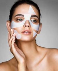 Charming woman with cotton facial mask. Portrait of beautiful young brunette touching hand her face. Skin care concept