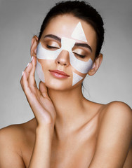 Young sensual lady with cotton facial mask on gray background. Photo of brunette woman touching hand her face. Skin care concept.